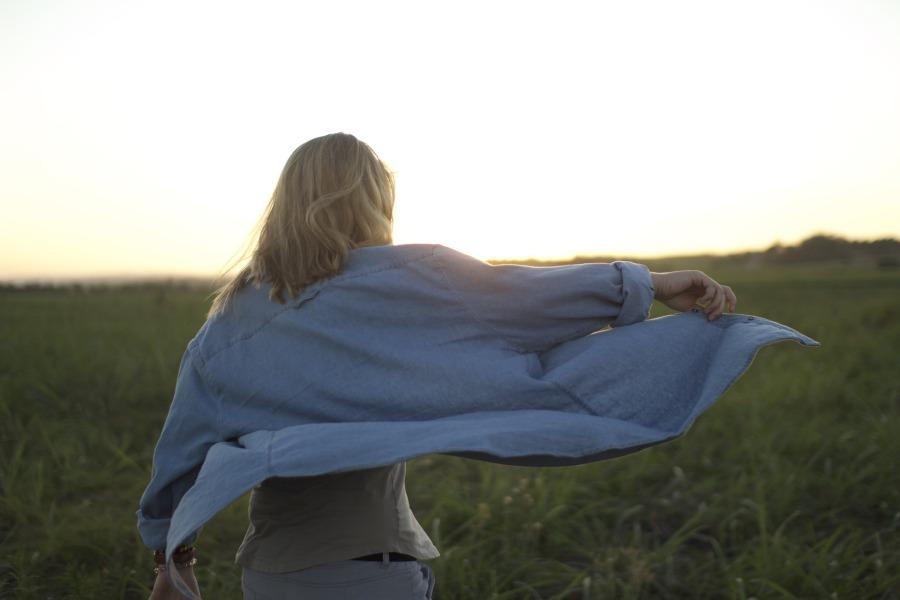 single woman alone walking in field in wind | the lonely tribalist