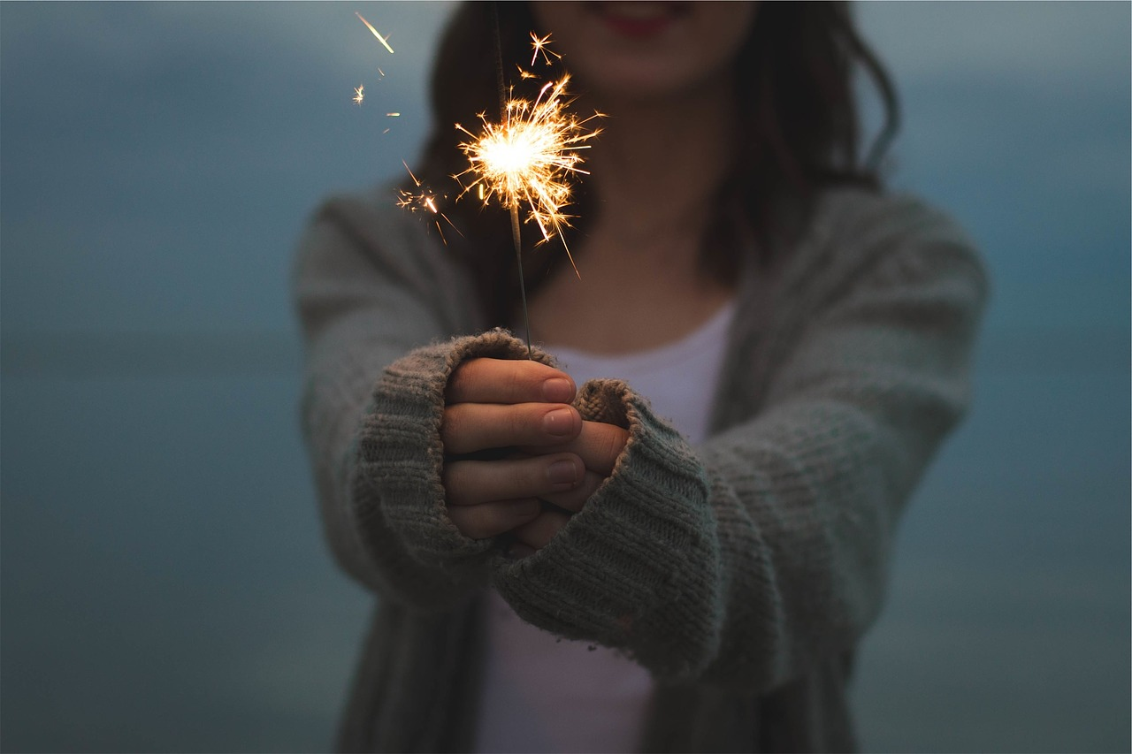 girl holding fire sparkler beach | the lonely tribalist